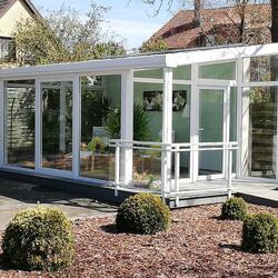 Kunststoffwintergarten Weiß im Wintergartenpark Celle mit Vordach und Geländer